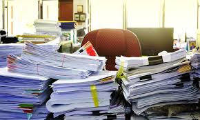 Desk overflowing with paper work